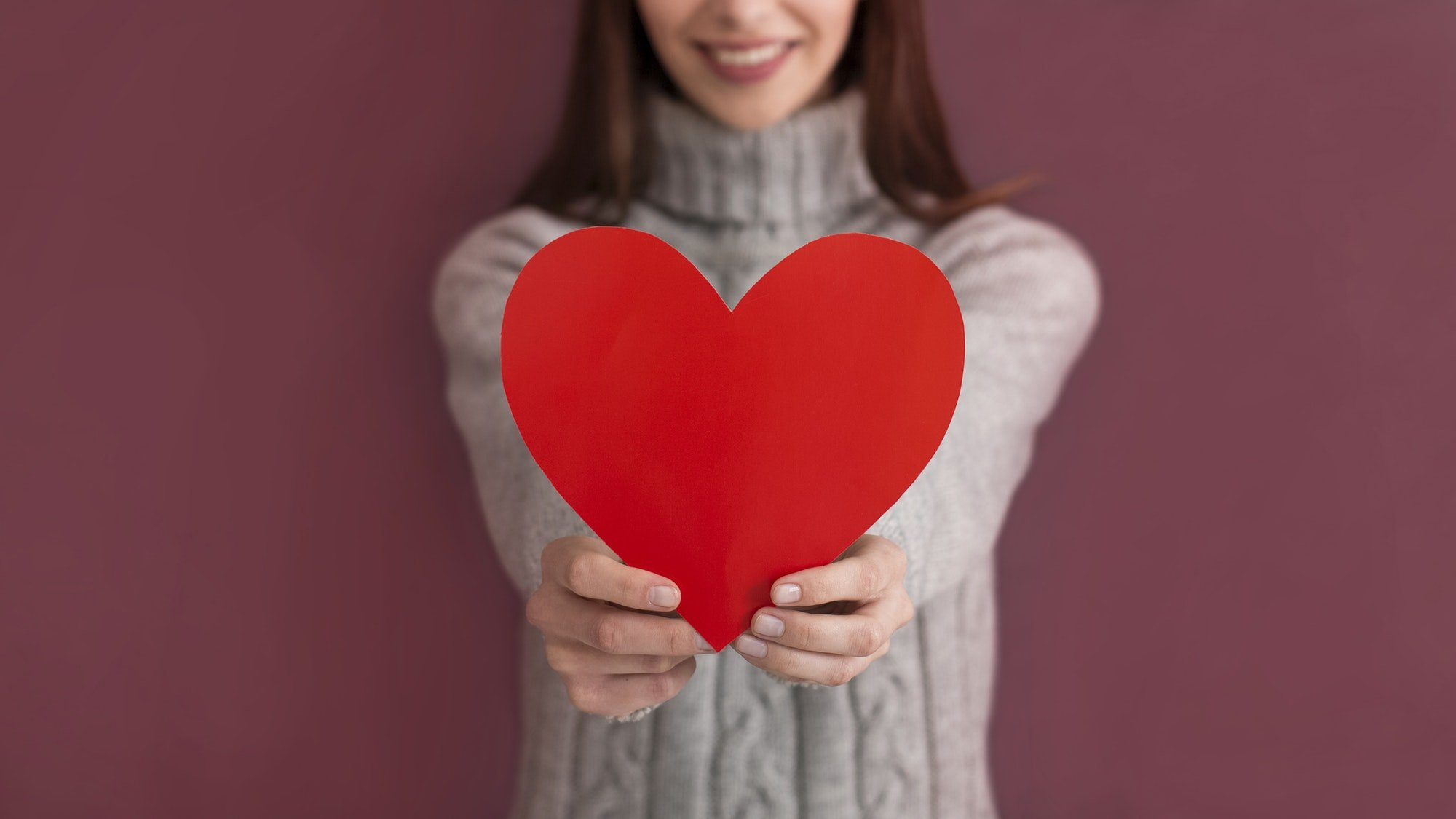 Cropped view of caucasian girl holding heart shaped card